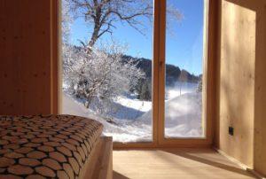 Schlafzimmer mit Doppelbett und Ausblick in die Natur