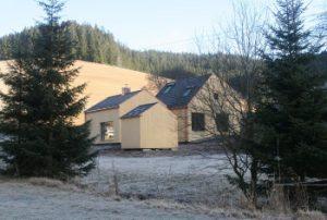 Man blickt vom Waldrand auf das Ferienhaus am früheren Seilerhansenhof